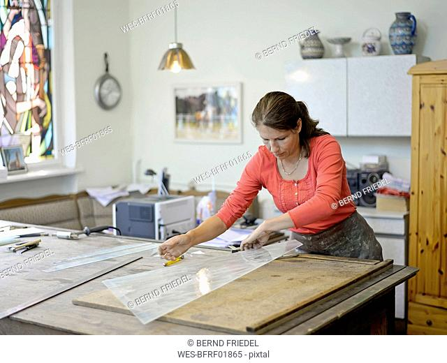 Woman working on glass pane in glazier's workshop