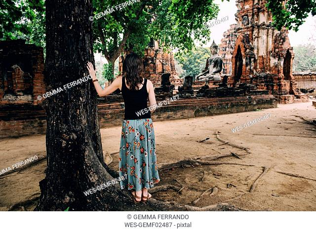 Thailand, Ayutthaya, Woman looking at a Buddha statue at Wat Mahathat