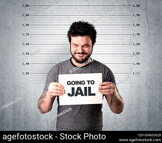 Caugth offender in front of a wall with table in his hand