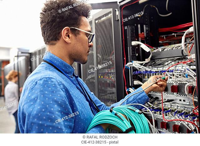 Male IT technician plugging cable into panel in server room