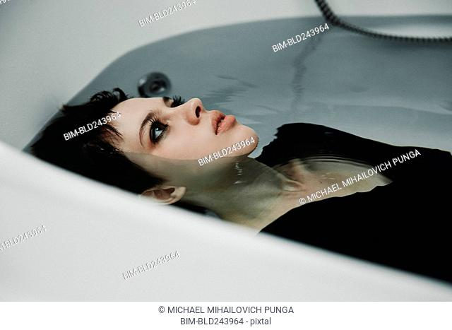 Caucasian woman wearing dress in bathtub