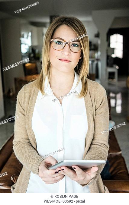 Portrait of smiling woman holding tablet at home