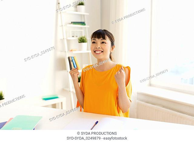 asian student girl celebrating success at home