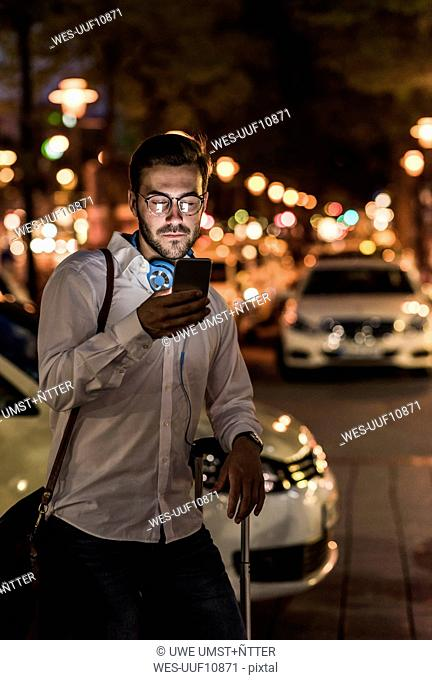 Young man in the city checking cell phone at night
