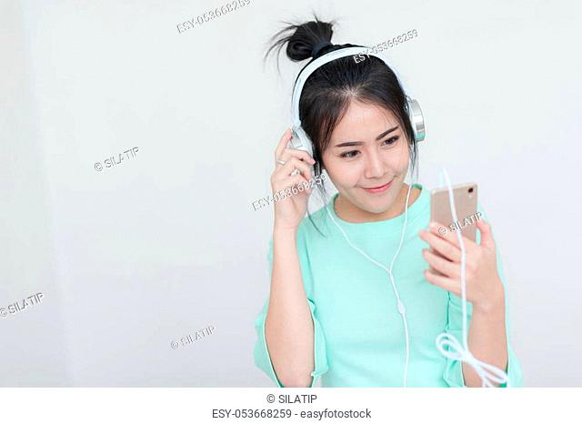 Young attractive Asian woman listening music on headphone while using smartphone for social network. Internet of things for modern lifestyle concept