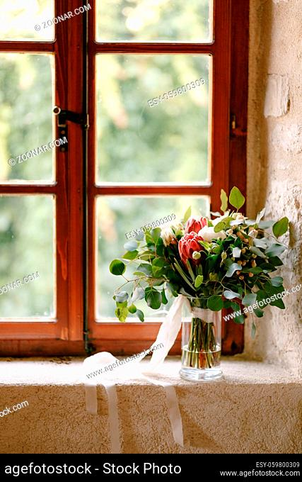 bridal bouquet of white peonies, roses, pink protea, snowberry, branches of eucalypt tree and white ribbons on the window. High quality photo