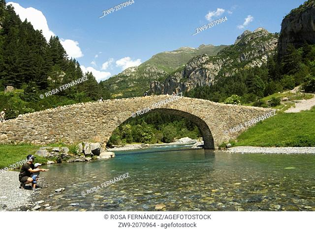 Father and son, medieval bridge over Ara river, Bujaruelo valley, Ordesa and Monte Perdido National Park
