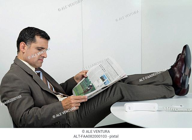 Businessman reading newspaper in office with feet up on desk