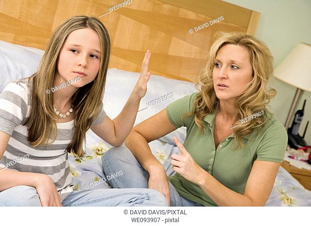 Caucasian mother and preteen daughter arguing while setting on bed an master bedroom