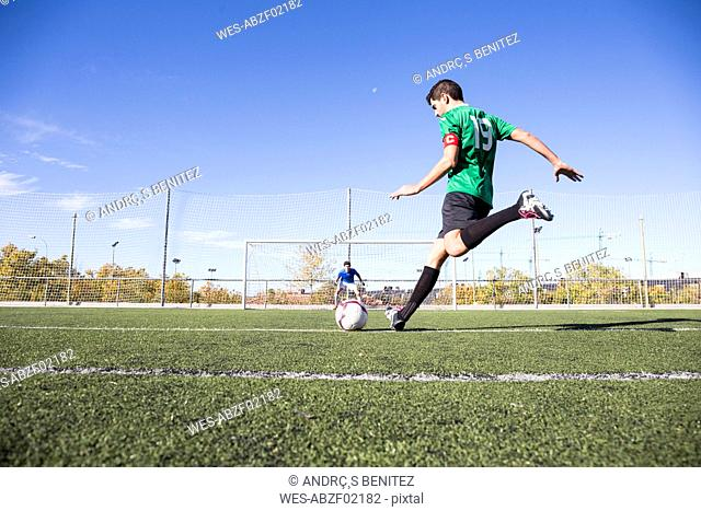 Football player shooting the ball on football field