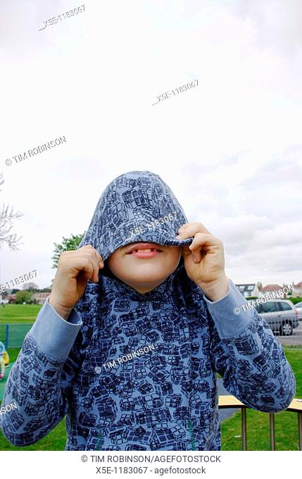 9 year boy fooling around in playground covering his face with hood