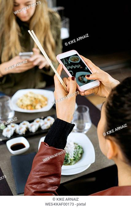 Woman taking picture of sushi in a restaurant, partial view