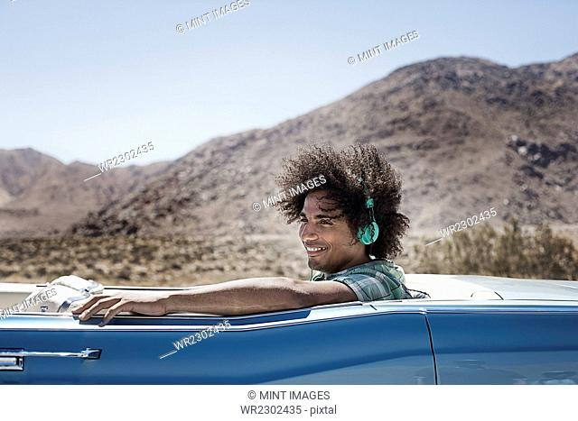 A young man with music headphones sitting in the back of a pale blue convertible on the open road in the mountains