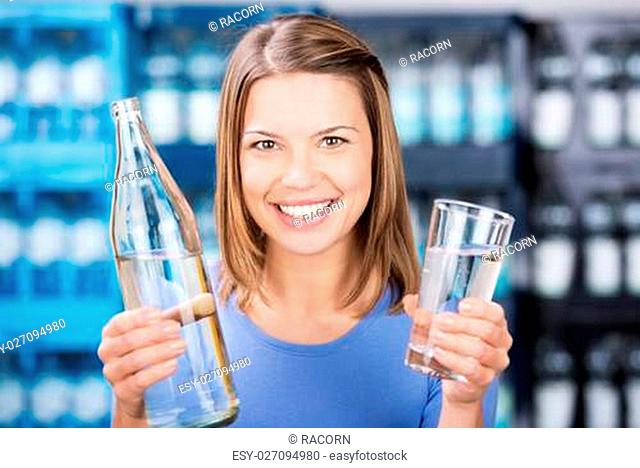 Smiling woman holding water bottle and glass in a close up shot