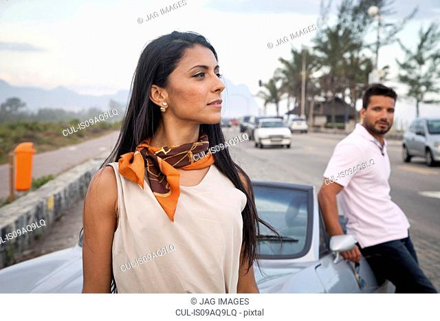 Mid adult couple standing by convertible car by side of road