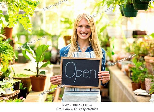 Young woman holding open sign placard at greenhouse