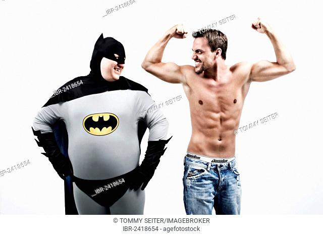 Overweight superhero laughing at a young muscular man