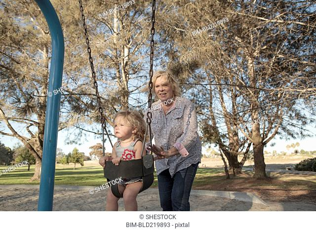 Grandmother pushing granddaughter on swing at playground