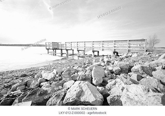 Wooden pier extending from rocky shoreline of lake