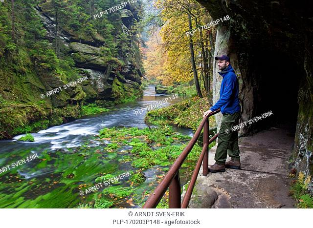Tourist visiting the Kamnitz Gorge / Soutesky Kamenice in Bohemian Switzerland in autumn, Ústí nad Labem Region / Ústecký Region, Czech Republic