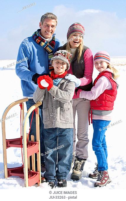 Portrait of smiling family with snowball and sled in snow