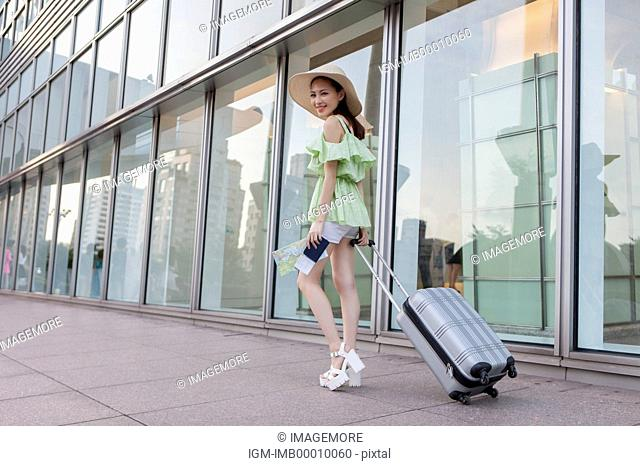 Young woman holding luggage and smiling at the camera