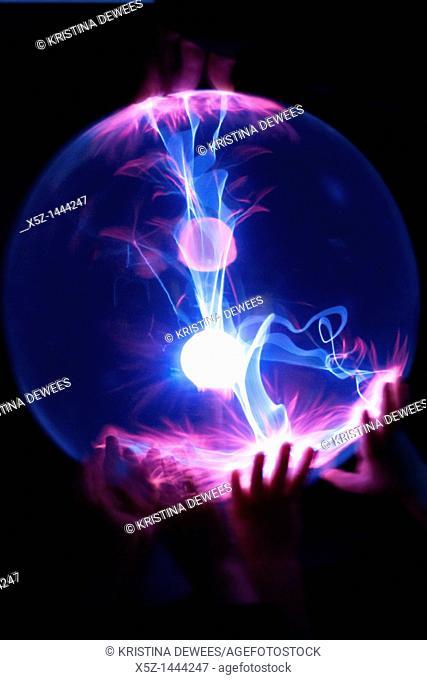 Children's hands on a Plasma Globe