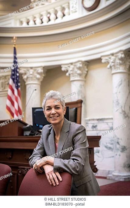 Caucasian politician smiling in capitol building