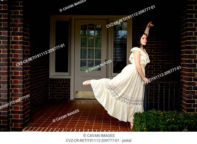 A dancer in a long white dress stands in arabesque on a shadowed porch