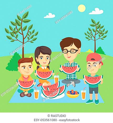 Young caucasian joyful mother with kids eating watermelon at the park during summer picnic. Happy children and their mother enjoying a watermelon outdoors