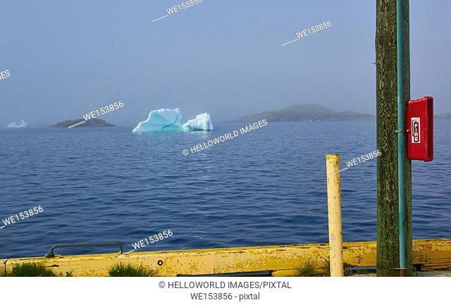 Fire extinguisher attached to telegraph pole with iceberg in mist in background, Newfoundland, Canada