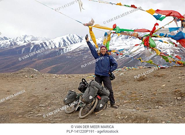 Proud female trekking cyclist conquered 4500 meter high mountain pass in the Himalayas on the Sichuan-Tibet Highway, Sichuan Province, China