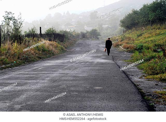 Armenia, Alaverdi, rear view of a man walking in the early morning, on an empty tar road in the countryside, with mountain range in the background and dark sad...
