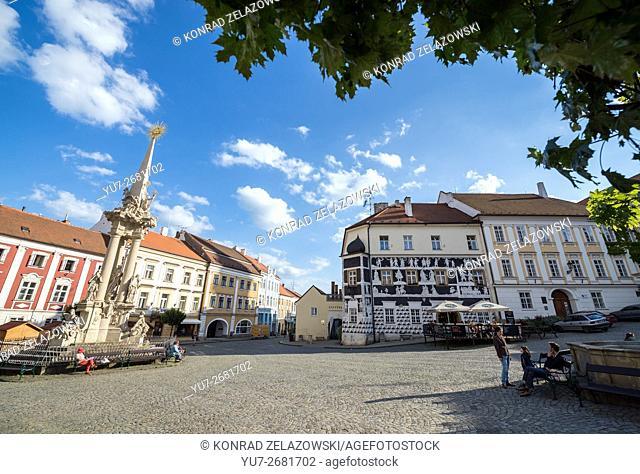 Holy Trinity Statue (called Plague Column) and Sgraffito house at central square in Mikulov, Moravia region, Czech Republic