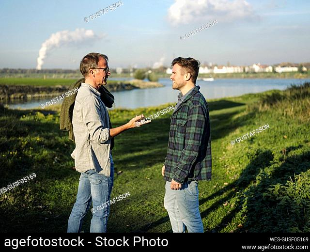 Father talking with son while standing on grass at riverbank