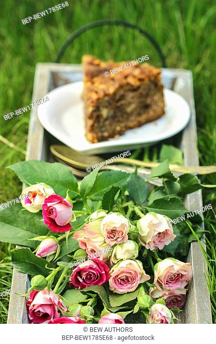 Garden party. Bouquet of pink roses and piece of cake on vintage wooden tray. Selective focus