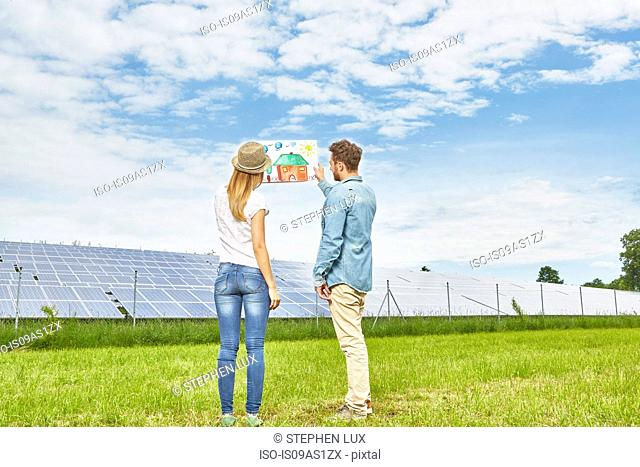 Young couple standing in field, looking at child's drawing of house, next to solar farm