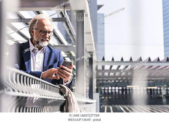 Smiling mature businessman in the city using cell phone