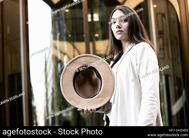 Portrait of woman with hat in hand. Munich, Germany