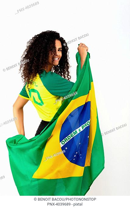 Portrait of a young supporter of the Brazil team wearing the national flag