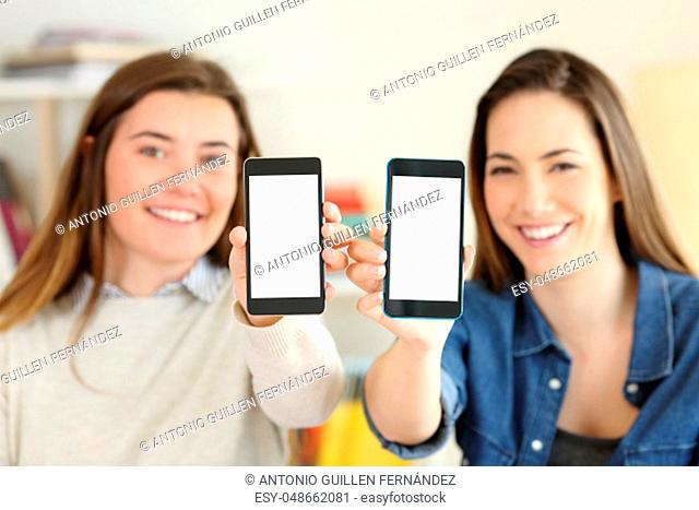 Two happy students showing their both smart phone screens to camera at home