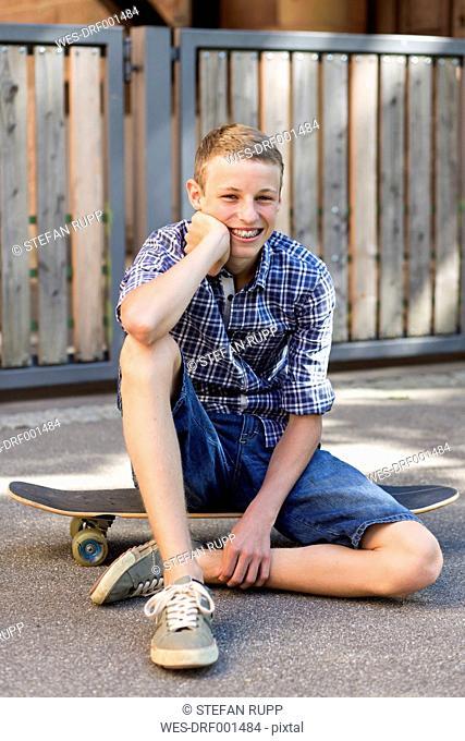 Smiling teenage boy sitting on skateboard