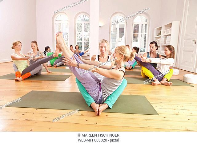 Group of people in yoga studio holding poses with their partners