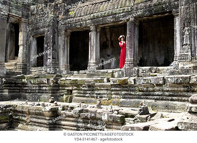 Tourist in Bayon Temple, complex of Angkor Thom, Siem Reap, Cambodia, Southeast Asia. Bayon is a well-known and richly decorated Khmer temple at Angkor in...