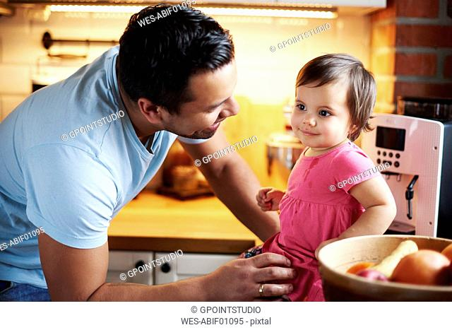 Smiling father looking at baby girl sitting on counter in kitchen at home
