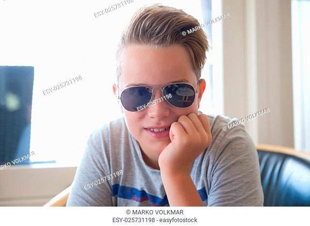 boy with sunglasses looking friendly in to the camera
