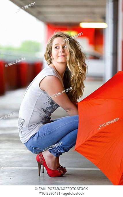 Young woman with Red umbrella squatting