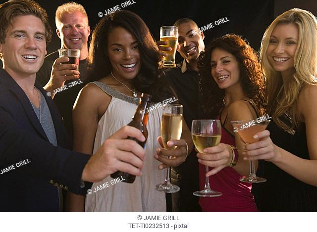 Portrait of friends celebrating with champagne at nightclub