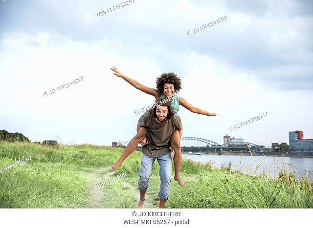 Germany, Cologne, happy carefree couple at the riverside