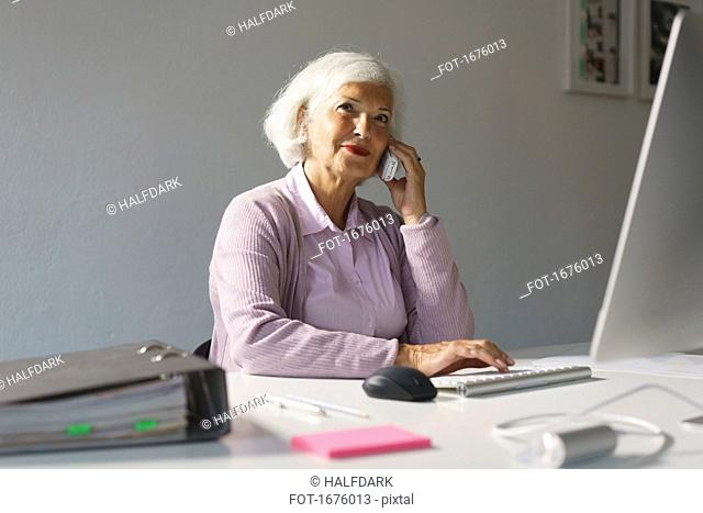 Smiling businesswoman using mobile phone while working on computer at office